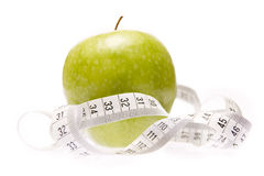 Apple with measuring tape. Apple entangled in measuring tape Royalty Free Stock Photos
