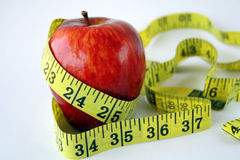 Apple with measuring tape arou. Nd in white background Royalty Free Stock Photos