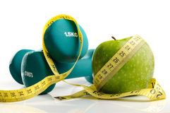 Apple, measuring tape and dumbbells isolated. Healthy apple, measuring tape and dumbbells for healthy living isolated Stock Photo