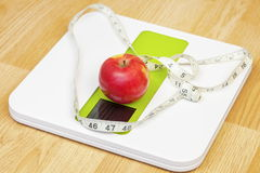 Apple with measuring tape on electronic scale.Diet concept. In room Royalty Free Stock Images