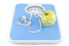 Apple and measuring tape on the floor scales i Royalty Free Stock Image