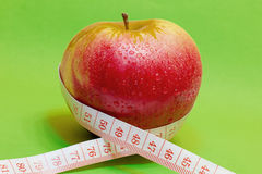 Apple and measuring tape. On green background stock image