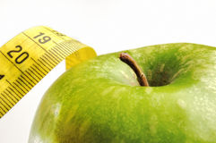 Apple and measuring tape for a healthy lifestyle 2. Apple and measuring tape isolated for a healthy lifestyle Stock Photography