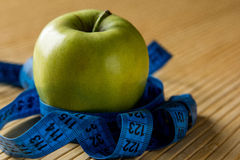 Apple and measuring tape on a light bamboo table. Green apple and measuring tape on a light bamboo table Stock Photography