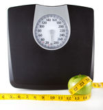 An Apple with a measuring tape and scale. An apple with a measuring tape around it with a scale in the background, white background. Room for copy-space on the Stock Photography