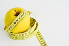Apple and measuring tape suggesting diet concept Royalty Free Stock Photos