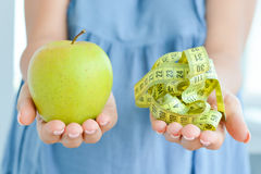 Apple and measuring tape suggesting diet concept Stock Photo