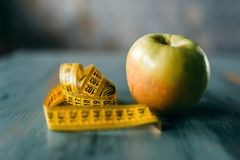 Apple and measuring tape, weight loss diet concept. Apple and measuring tape on wooden table closeup. Weight loss diet concept, fat burning Stock Photography