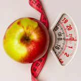 Apple with measuring tape on weight scale. Dieting Stock Image