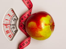 Apple with measuring tape on weight scale. Dieting. Dieting healthy eating slim down concept. Closeup apple with measuring tape on weight scale Stock Photography