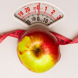Apple with measuring tape on weight scale. Dieting Royalty Free Stock Photography