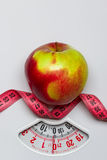 Apple with measuring tape on weight scale. Dieting Stock Photos