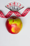 Apple with measuring tape on weight scale. Dieting Royalty Free Stock Image