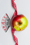 Apple with measuring tape on weight scale. Dieting. Dieting healthy eating slim down concept. Closeup apple with measuring tape on white weight scale Royalty Free Stock Images