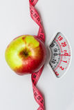 Apple with measuring tape on weight scale. Dieting Royalty Free Stock Images