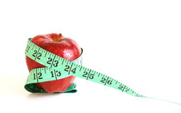 Apple and measuring tape on white background. Apple and measuring tape and white background royalty free stock image