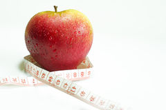 Apple and measuring tape. On a white background royalty free stock photography
