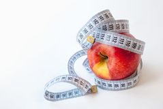 Apple and measuring tape on white background. Diet concept royalty free stock photos