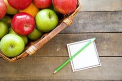 Apple med anteckningsboken på träbakgrund Royaltyfria Foton