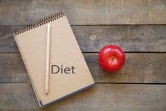 Apple med anteckningsboken på träbakgrund Arkivfoto