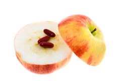 Apple and medicines. Some the red tablets lying on the cut apple Royalty Free Stock Photo