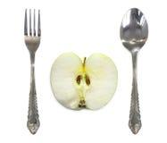 Apple mellan gaffeln och skeden Arkivfoto