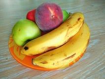 Apple, melocotón y plátano en la placa anaranjada Fotografía de archivo libre de regalías