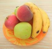 Apple, melocotón y plátano en la placa anaranjada Foto de archivo libre de regalías