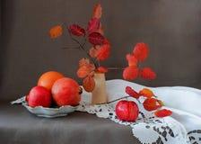 Apple, melograni e foglie di autunno in un vaso su un tovagliolo bianco Immagini Stock