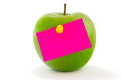 Apple with memo sticker. Green apple with bright pink memo sticker isolated on white Royalty Free Stock Image