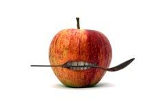 Apple met lepel tussen de tanden Stock Afbeeldingen