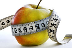 Apple and meter. Apple with meter wrapped around it. healthy lifestyle. White background Royalty Free Stock Photo