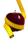 Apple and metric tape. Red apple surrounded by metric tape Royalty Free Stock Photo