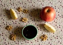 Apple, miel et écrous sur la table Photos stock