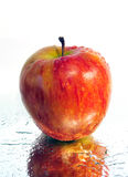 Apple on the mirror. Apple in water droplets lies on the mirror surface Stock Photo