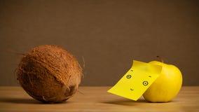 Apple mit der Haftnotiz, die Kokosnuss betrachtet Stockfoto