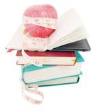 Apple mit Maßband auf großem Stapel der Bücher Stockfotos