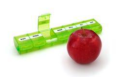Apple mit Pillen-Organisator stockfoto