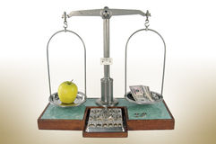Apple and money balanced scale. Apple and money balancedtraditional old style pharmacy scale with small weights Royalty Free Stock Image