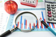 Apple, money,clock, telephone and calculator placed on document. Royalty Free Stock Image