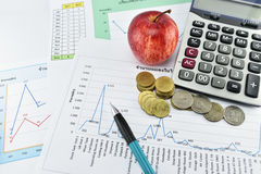 Apple, money,clock, telephone and calculator placed on document. Royalty Free Stock Photos