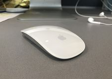 Apple Mouse. Closeup of an apple mouse next to a Mac computer and headphones royalty free stock image