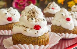 Apple muffins. With whipped cream and cinnamon sprinkles with candy faces stock photography