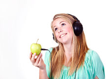 Apple music. Girl listening to music from an apple royalty free stock photos