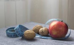 Apple, Nüsse und Maßband für Verlustgewicht Lizenzfreie Stockbilder