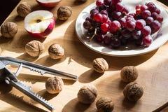 Apple, Nüsse und Traube auf Holztisch lizenzfreies stockfoto