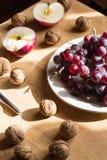 Apple, Nüsse und Traube auf Holztisch lizenzfreie stockbilder