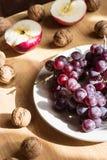 Apple, Nüsse und Traube auf Holztisch stockfotos
