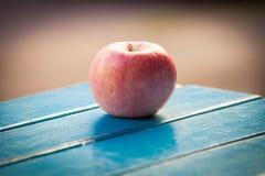Apple na tabela de madeira Imagens de Stock