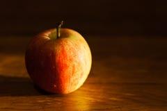 Apple na tabela iluminada pela luz solar da tarde Foto de Stock Royalty Free